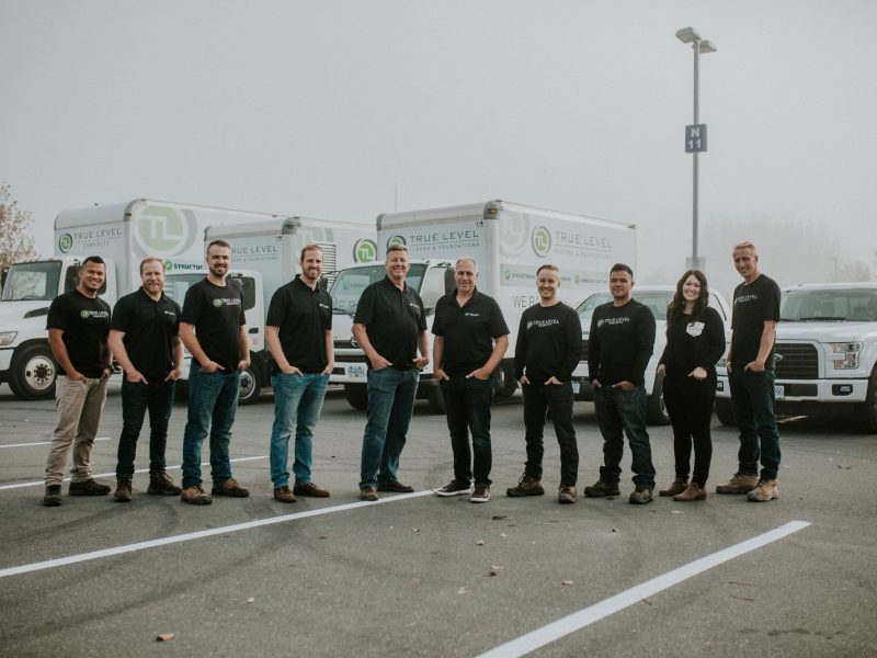 True Level Concrete team posing in front of service trucks